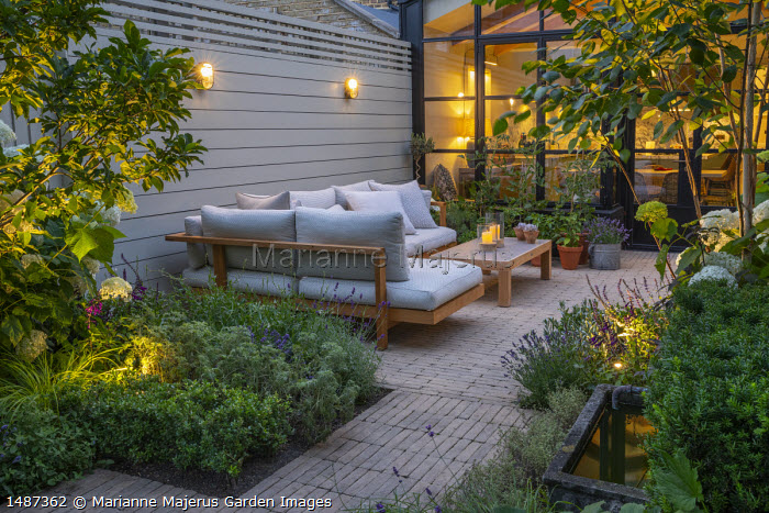 Timber furniture with cushions on stone paving, stone trough with fountain