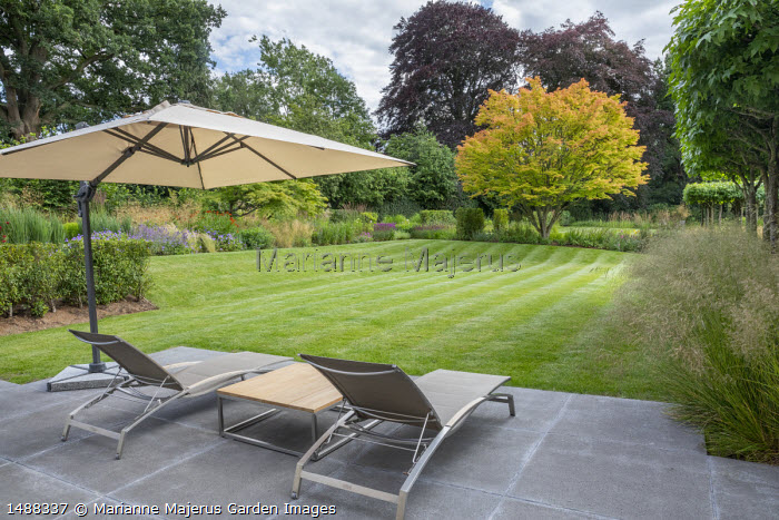 Contemporary recliner chairs under umbrella on concrete patio, mowing stripes on lawn, acer