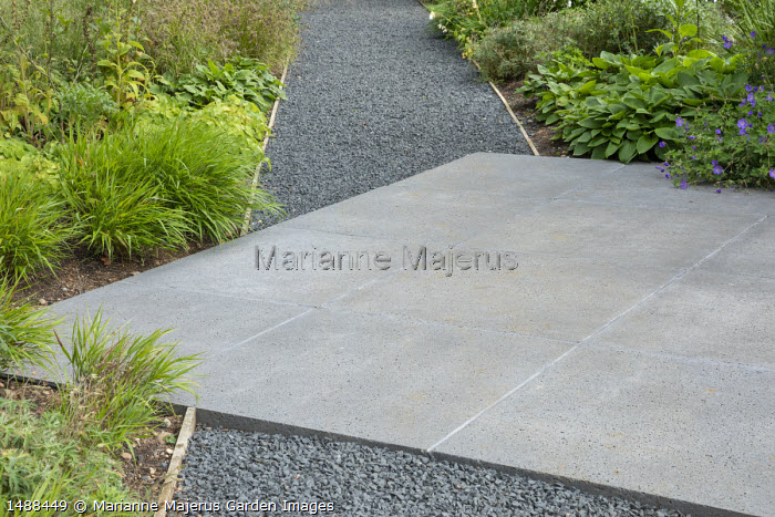 Diagonal concrete paving square in gravel path, Hakonechloa macra, hosta, geranium