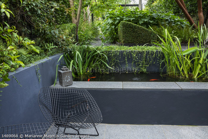 Raised fish pond, metal wirework chair on stone patio
