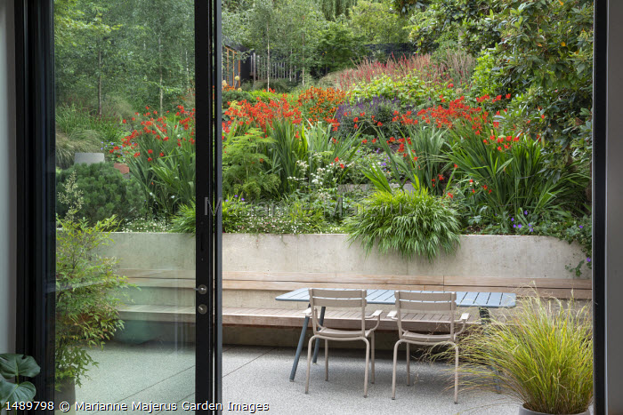 View from inside house to table and chairs on patio outside, built-in bench, Crocosmia 'Lucifer', Selinum wallichianum, Hakonechloa macra, Anemanthele lessoniana in pot