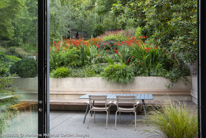View from inside house to table and chairs on patio outside, built-in bench, Crocosmia 'Lucifer', Hakonechloa macra