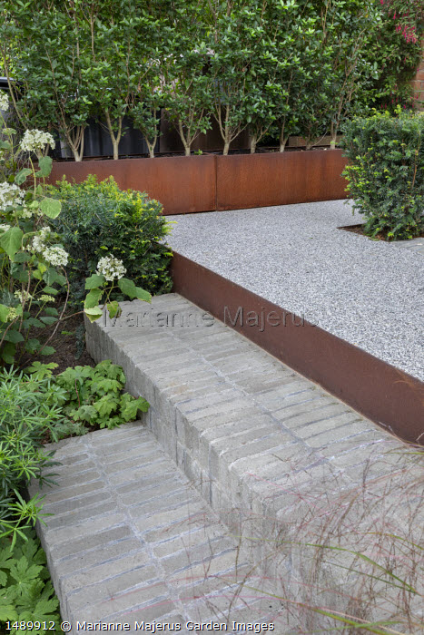 Brick steps, raised gravel terrace edged with Cor-Ten steel, clipped yew hedges