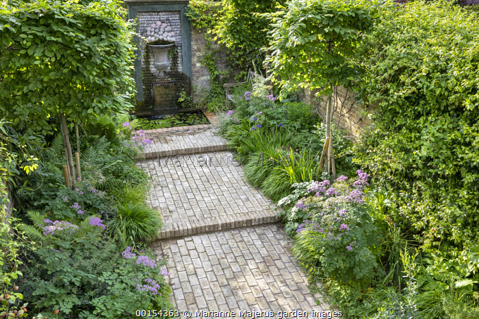 Brick path leading to shell water fountain in enclosed town garden, Hakonechloa macra, wooden bench, pleached hornbeam screens