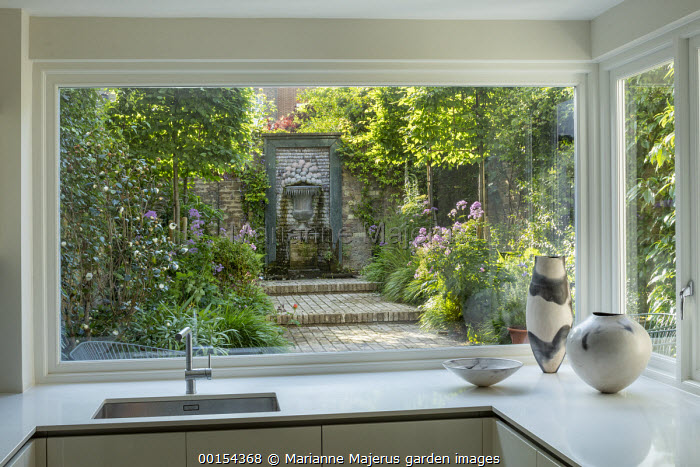 View from inside house through window to enclosed courtyard garden outside, brick path leading to shell water fountain, Hakonechloa macra, aquilegia, pleached hornbeam screens
