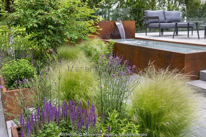 Stipa tenuissima, salvia and verbena in Cor-Ten steel raised beds, Amelanchier lamarckii, raised pond and fountain by chairs on terrace