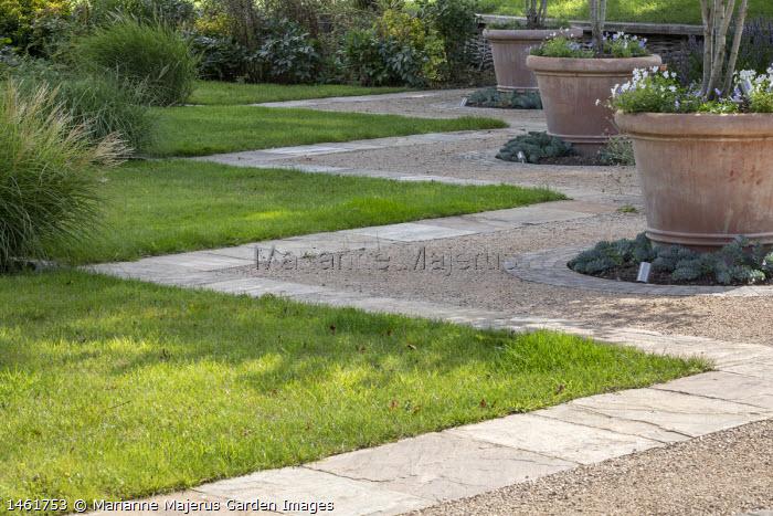 Stone zig-zig lawn edging, violas in large terracotta pots, Euphorbia myrsinites