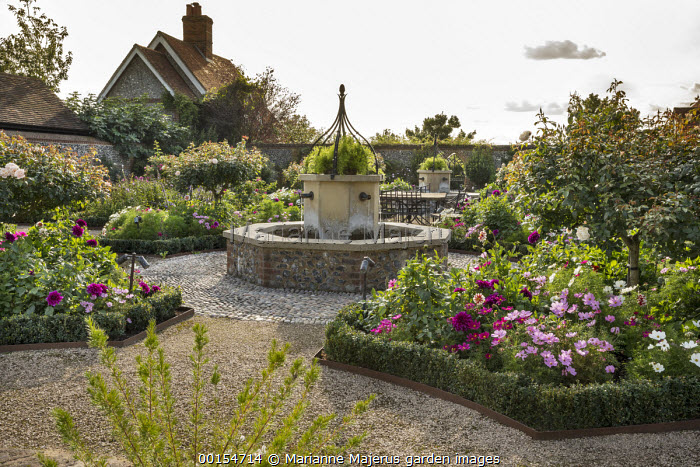 Water fountain in rose garden, Cosmos bipinnatus in box-edged borders, gravel paths edged with Cor-Ten steel
