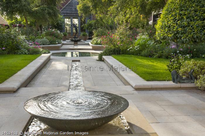 Bubbling water container, rill leading to circular pond, stone patio, view to sculpture, Rosa x odorata 'Mutabilis', Cosmos bipinnatus, phlox