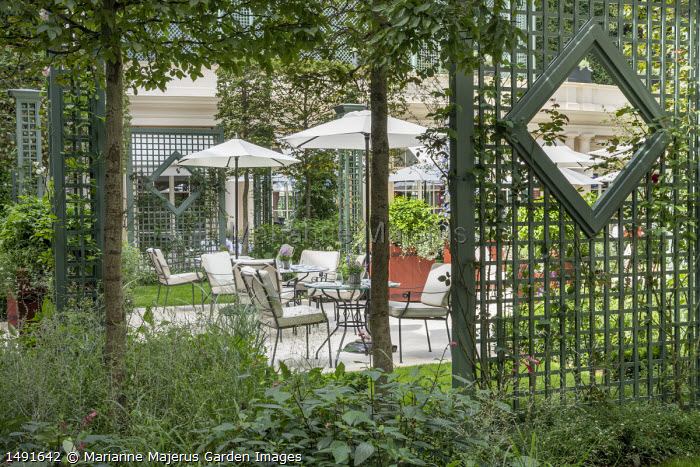 View through row of pleached Carpinus betulus trees, green painted trellis screens, tables and chairs on stone terrace under umbrellas
