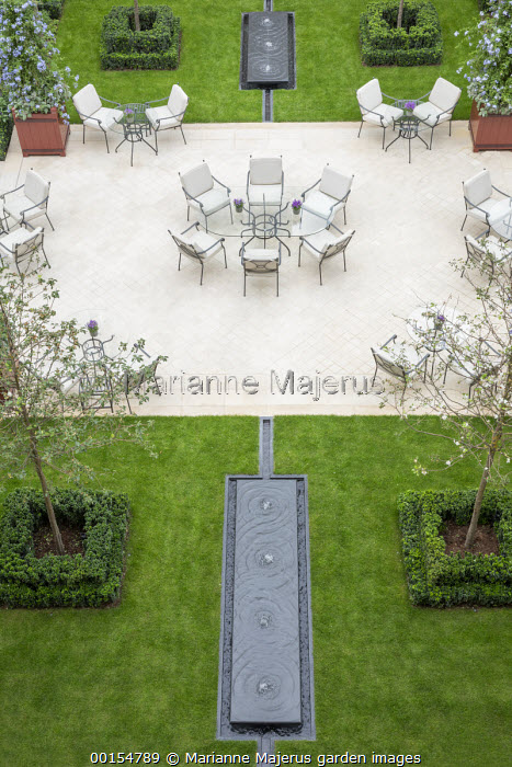 Tables and chairs on stone terrace, bubbling contemporary water fountains in lawn, Malus 'Evereste' in Euonymus japonicus 'Microphyllus' edging