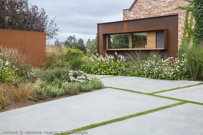 White garden, Anemone x hybrida 'Honorine Jobert', hosta, Cor-Ten steel clad house, polished concrete paving