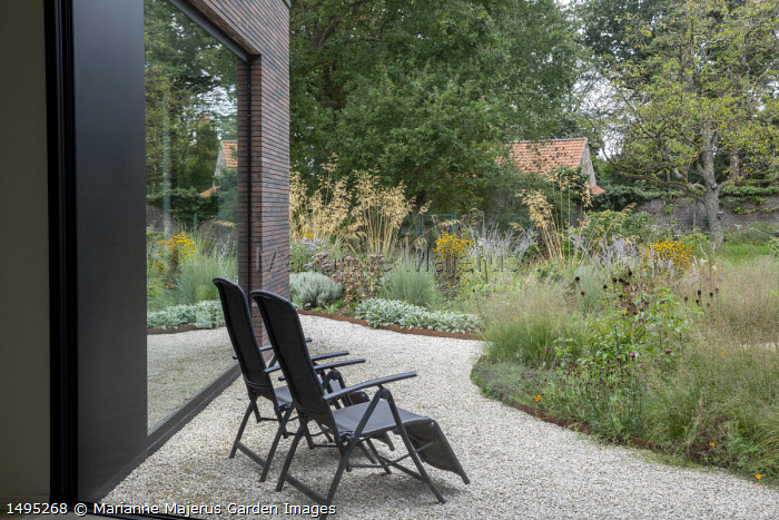Chairs on gravel terrace by house, borders edged with Cor-Ten steel, Stipa gigantea