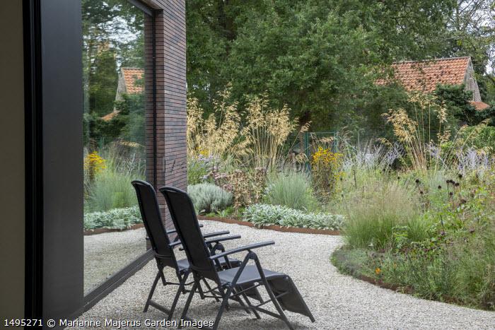 Chairs on gravel terrace by house, borders edged with Cor-Ten steel, Stipa gigantea, Echinacea pallida seedheads, Sporobolus heterolepis 'Wisconsin Strain', Stachys byzantina, Eryngium giganteum seedheads