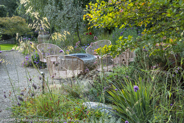 Table and chairs on gravel terrace, Verbena bonariensis, Stipa gigantea