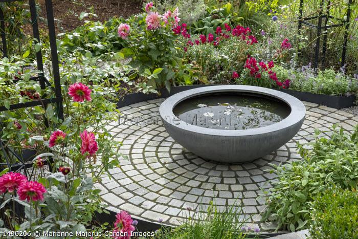 Raised pond in container on circular limestone sett patio, sage, dahlias, Urbis Lilybowl water bowl