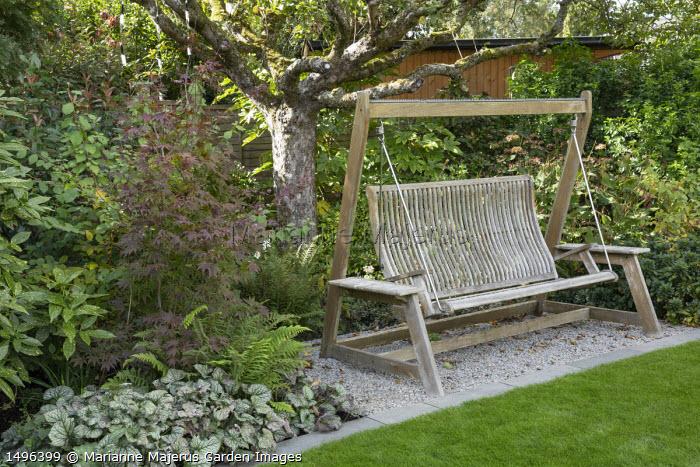 Hanging swing seat on gravel terrace under apple tree, Acer palmatum 'Atropurpureum', Polystichum setiferum, Brunnera macrophylla 'Jack Frost'