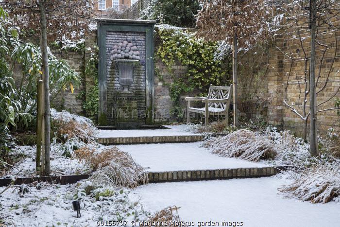 Formal town garden, pleached hornbeam screens, shell fountain, wooden bench, wide brick steps, Hakonechloa macra