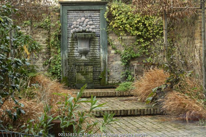 Formal town garden, shell fountain, wooden bench, wide brick steps, Hakonechloa macra