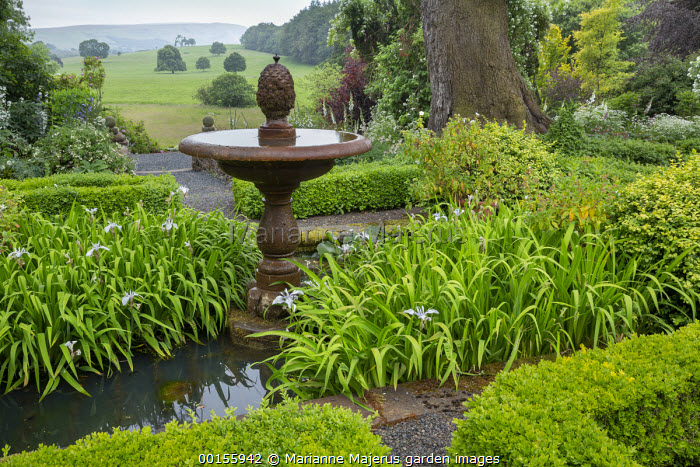 Stone water fountain in centre of box parterre, irises, view across countryside