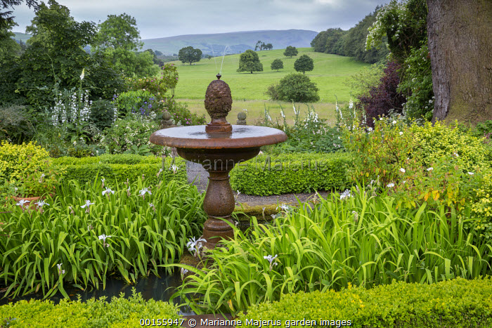 Stone water fountain in centre of box parterre, irises, view across countryside, foxgloves