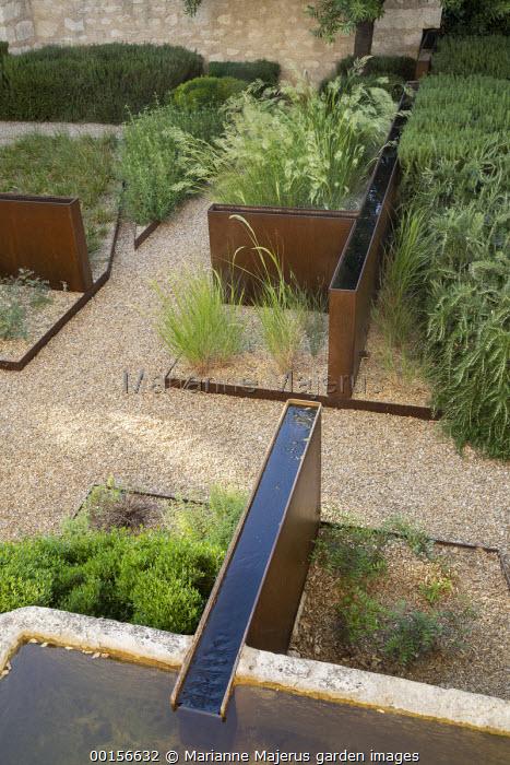 Raised steel rills in mediterranean courtyard garden, gravel paths and mulch, steel border edging, stone trough