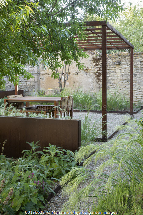 Wooden table and chairs on gravel terrace under steel pergola, stone wall, raised metal rill, Stipa calamagrostis