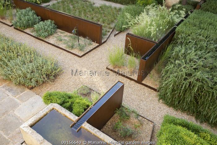 Overview of contemporary mediterranean terrace, raised steel rills, gravel paths and mulch, steel border edging, Rosmarinus officinalis, Stipa calamagrostis