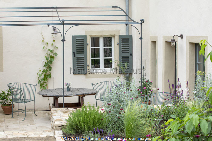 Metal chairs and wooden table under metal pergola attached to house, rosemary, Stipa tenuissima, Dianthus cruentus, Salvia nemorosa 'Caradonna' and artemisia in border