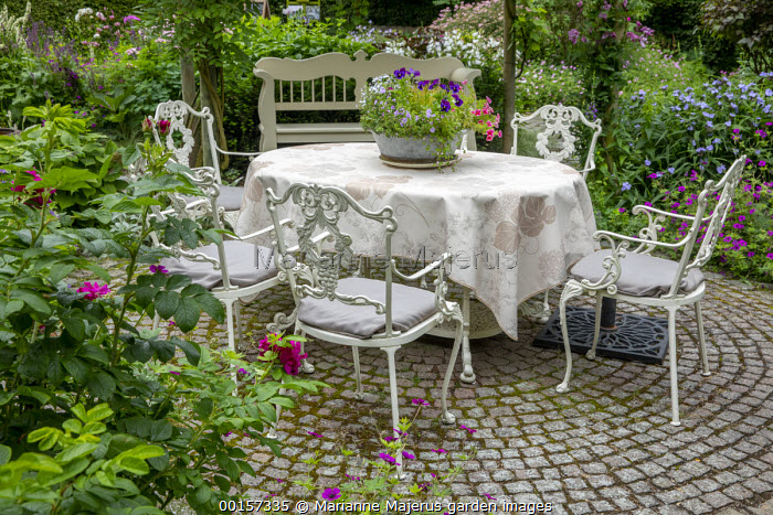 Metal table and chairs on circular stone sett patio, wooden bench, Geranium 'Anne Thomson', petunias in pot, tablecloth, Tradescantia (Andersoniana Group) 'Blue Stone'