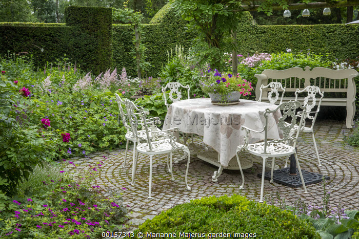 Metal table and chairs on circular stone sett patio, wooden bench, Geranium 'Anne Thomson', Astilbe 'Dito', petunias in pot, tablecloth, garden 'room'