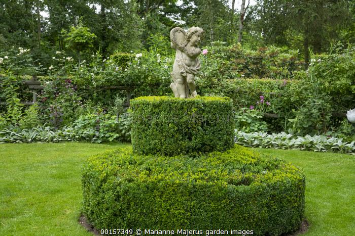 Clipped Buxus sempervirens topiary around stone cherub statue, garden 'room'