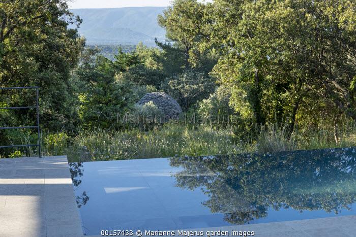 Infinity pool in mediterranean garden, stone sculpture