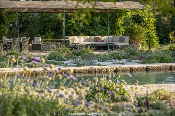 Stone paving slabs in mediterranean gravel garden, outdoor sofas under gazebo shelter, swimming pool