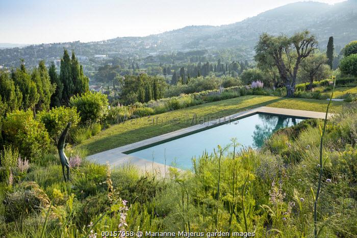 View to swimming pool terrace on mediterranean hillside garden