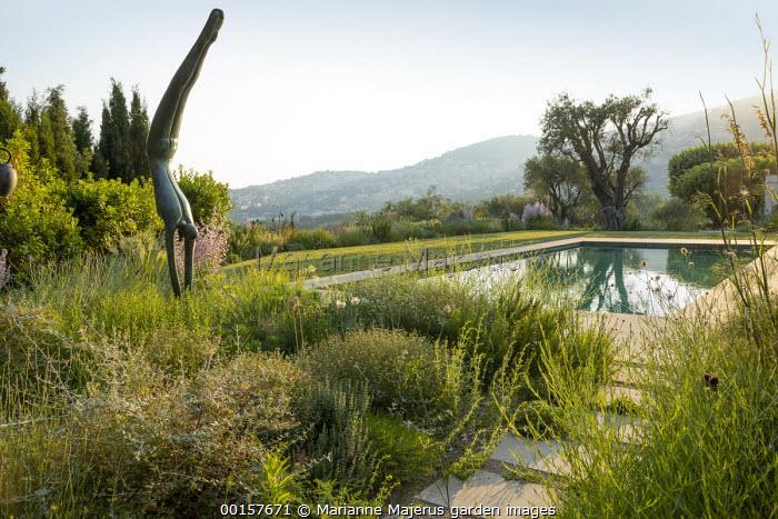 View across swimming pool in terraced hillside garden to landscape beyond