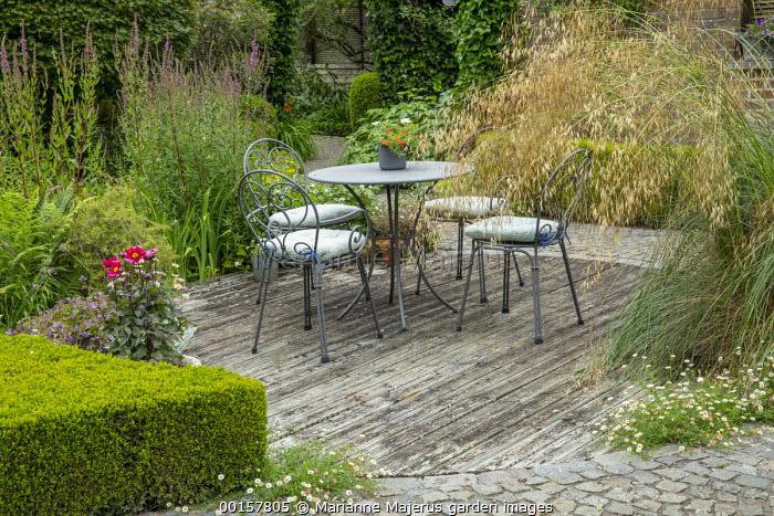 Metal table and chairs with cushions on decking, Stipa gigantea, Erigeron karvinskianus in cracks, dahlia, garden 'room'