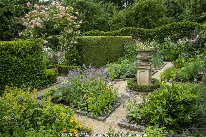 Stone urn on plinth in potager, Rosa 'Phyllis Bide' climbing over metal arch, garden 'room', stone border edging, Borago officinalis, nasturtiums, marigolds
