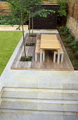 Steps up to contemporary table and benches on decking, limestone water wall, Cercidiphyllum japonicum, paving