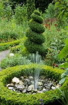 Spiral box topiary, box-edged pebble fountain