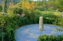 Low box hedge, circular slate and pebble sundial patio, achillea, Verbena bonariensis, asters