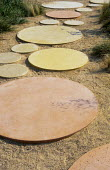 Large circular disks, stepping stone path, sandy mulch