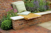 Wooden wall seat, cushions, bricks, raised bed with herbs