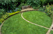 Curved lawn with brick edging, bench