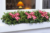 Holly and mistletoe decoration with red and white bows on windowsill