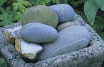 Pebbles in stone trough, objet trouvé