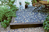 Raised patio edged by railway sleeper, slate paddlestones, stool, container with lavender