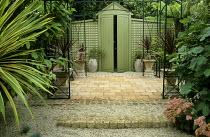 'Mediterranean' patio garden, gravel, terracotta tiles, cordyline, fig, doorway, trellis