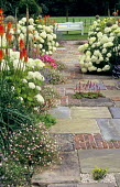 Brick and stone path, Hydrangea arborescens 'Annabelle', kniphofia, erigeron, view to bench