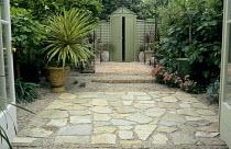 View through french doors to 'Mediterranean' patio garden, York stone crazy paving, cordyline, fig, doorway